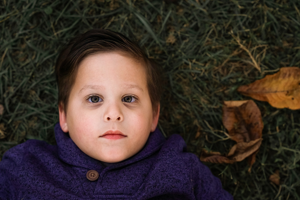 little boy laying in grass with fall leaves