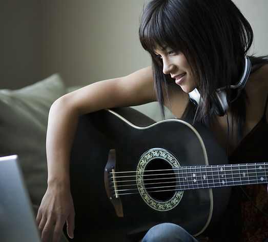 Woman holding acoustic guitar and using