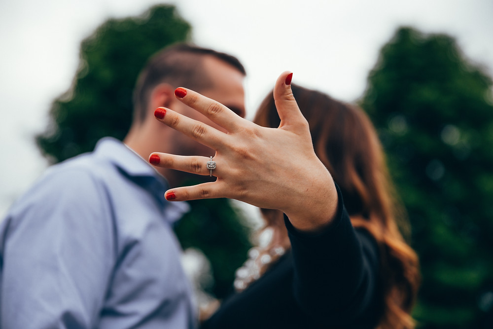 Shallow focus of man and woman kissing each other, showing hand to camera with engagement ring