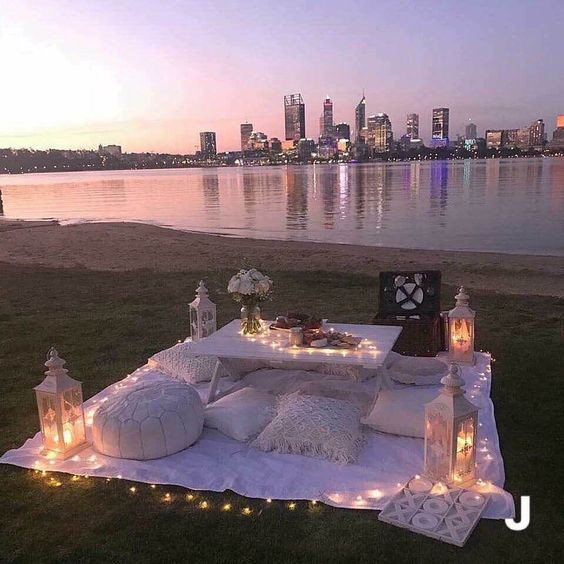 Romantic picnic looking out on to the water and a city view at sunset.