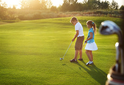 casual-kids-at-a-golf-field-holding-golf-clubs-48870371