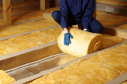 Construction worker thermally insulating house attic with glass wool .jpg