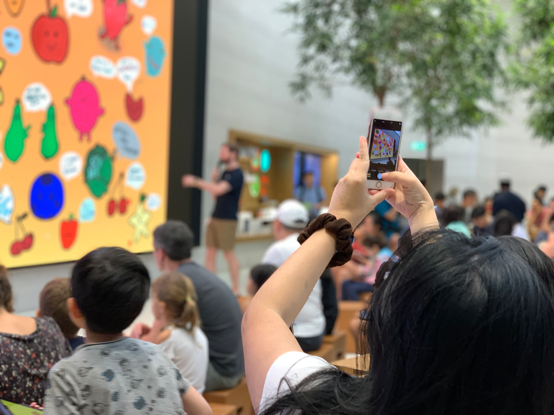 A lady photographing the final artworks on the screen.