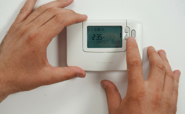 Hands setting thermostat temperature
