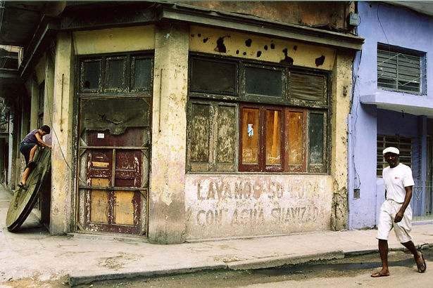 A Photograph by Alan Reich showing a man walking on th streets of Cuba while a young child climbs a wheel