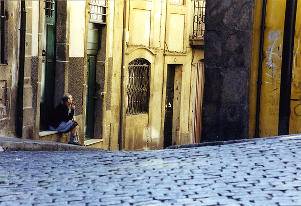 A Photograph by Alan Reich, showing a woman seated on the doorstep and a cobble stone street in Porto