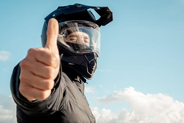 Motorcyclist wearing a black dual-purpose motorcycle helmet with a black jacket with sky b