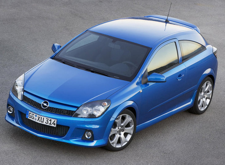 Blue Opel Astra driving on a road