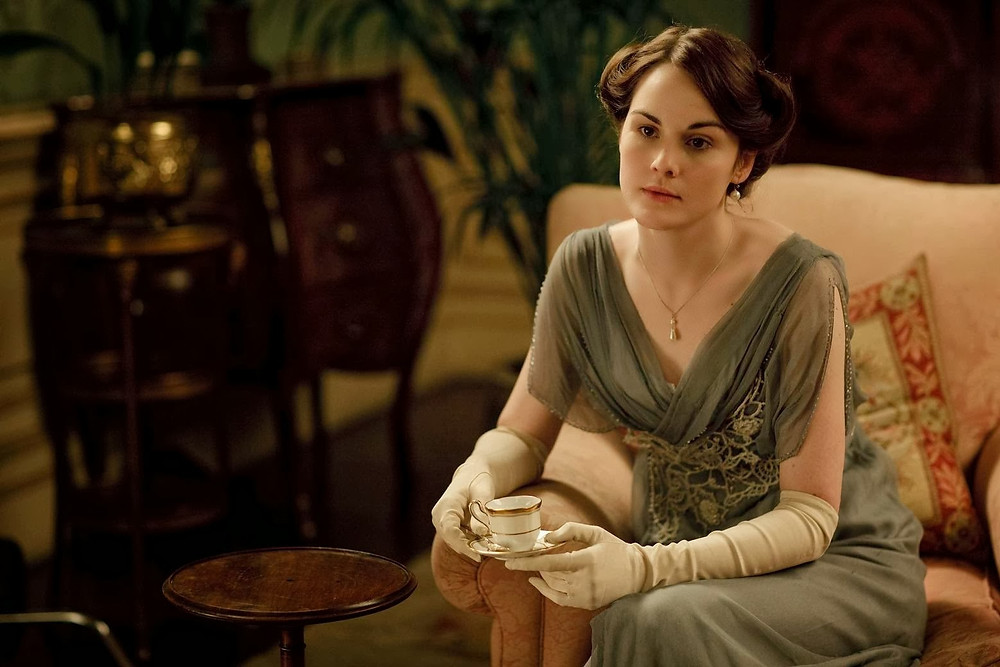 "Lady Mary exhibiting a ""no no"" in glove etiquette in this scene from Downtown Abbey. Proper glove etiquette suggests gloves off when eating and drinking.  Photo courtesy of Etiquette with Maura Graber."