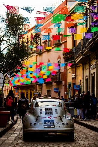 Classic Porsche 356 driving through colourful streets in America