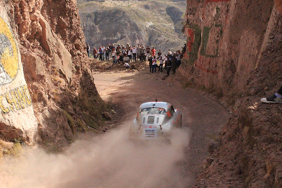 Classic Porsche 356 rally racing through South America with dust cloud