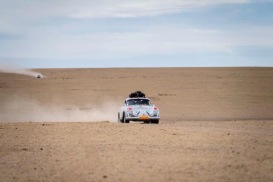 Classic Porsche 356 rally racing through a deserted desert