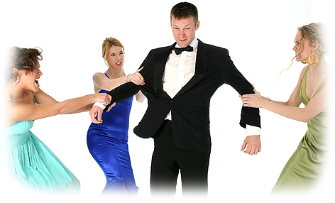 A man in tuxedo with dressed up women pulling on arms.