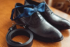 Dress shoes and rolled belt on table