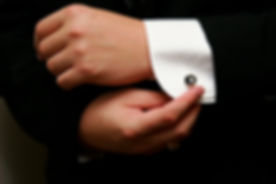 Close up of man in tuxedo buttoning sleeves