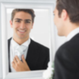 Man in tuxedo looking at reflection in mirror