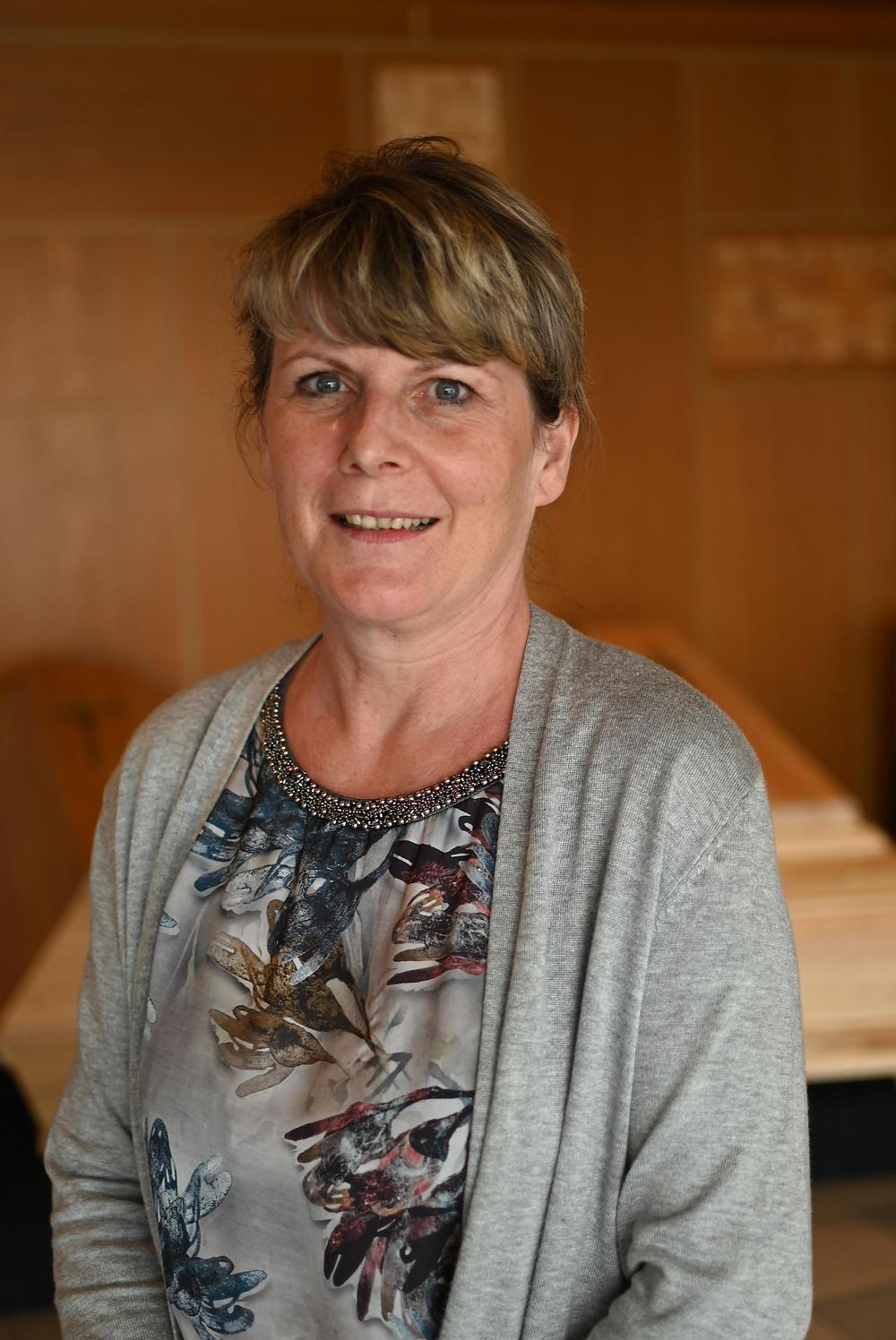 Christine Esterbauer steht im Ausstellungsraum und lächelt in die Kamera. Ein Porträtfoto.