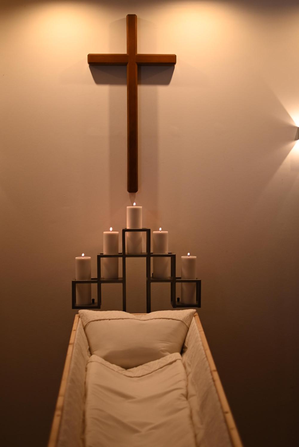 Der Abschiedsraum. Ein weiß ausgepolsterter Sarg, am Kopfende stehen fünf Blockkerzen in einer Halterung, an der Wand über dem Sarg hängt ein schlichtes Holzkreuz. Von der Decke kommt schummriges Licht.