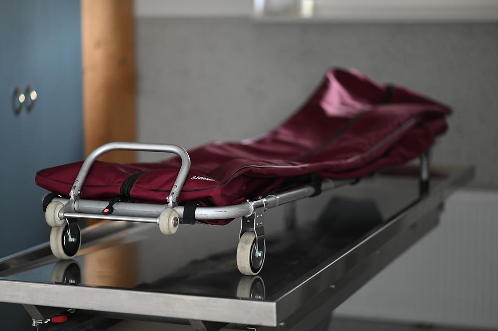 Eine Bergetrage für den Transport von Verstorbenen steht auf einem stählernen Waschtisch. Die Bergetrage hat Rollen und einen dunkelroten, vershließbaren Bezug, in den eine verstorbene Person gelegt werden kann.