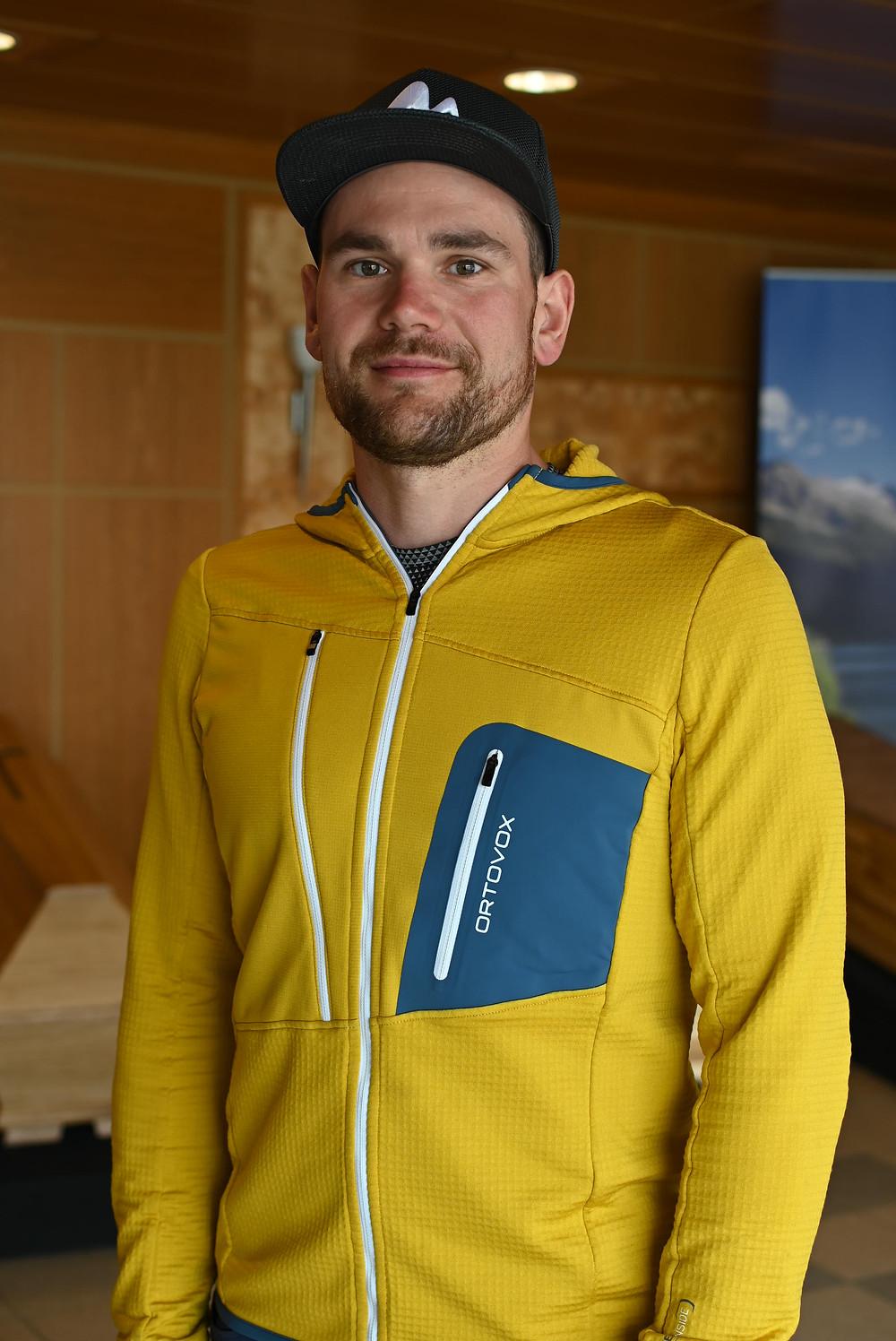 Reinhold Esterbauer steht im Ausstellungsraum vor den Särgen, im Hintergund ist eine Bergfotografie auf einem Banner zu erkennen. Reinhold lächelt in die Kamera. Ein Porträtfoto.