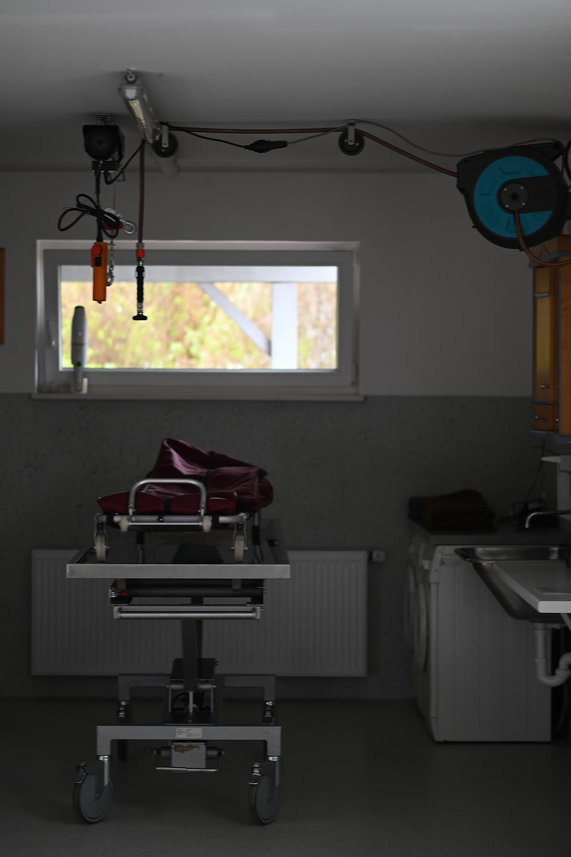 Die Waschnische. Auf einem stählernen Waschtisch mit Rollen steht eine Bergetrage. Von der Wand darüber hängt ein Wasserschlauch und ein Gerät zum Heben schwerer Objekte (in diesem Fall für die Körper verstorbener Menschen). Rechts an der Wand ist eine Waschmaschine und ein Waschbecke.n