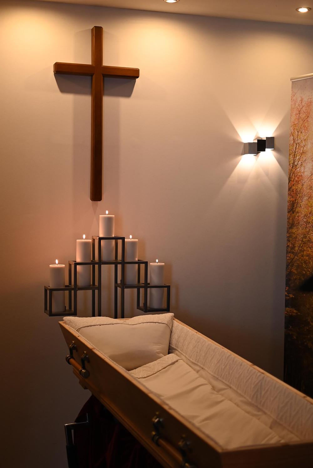 Das Abschiedszimmer. Ein hölzernes Kreuz hängt an der Wand, darunter steht ein weiß ausgepolsterter Sarg, fünf Blockkerzen stehen in einer Halterung am Kopfende. Rechts neben dem Kreuz hängt eine Wandleuchte, von der Decke strahlt ebenfalls schummriges Licht.