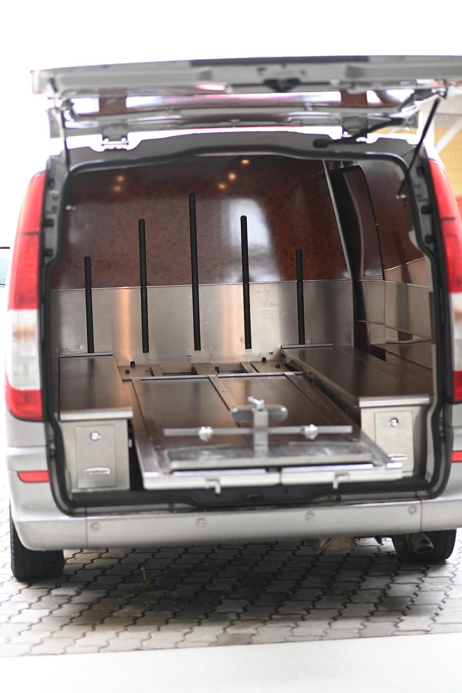 Ein Bestattungsfahrzeug mit offener Heckklappe. Im Inneren gibt es einen Schienenmachanismus, um Bergetragen und Bergesärge zu befestigen.
