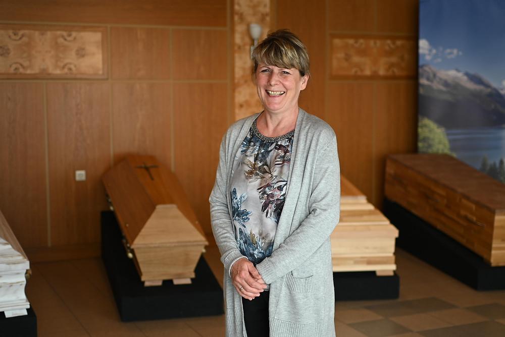 Christine Esterbauer steht im holzvertäfelten Ausstellungsraum vor den Särgen. Sie lacht herzlich in die Kamera.
