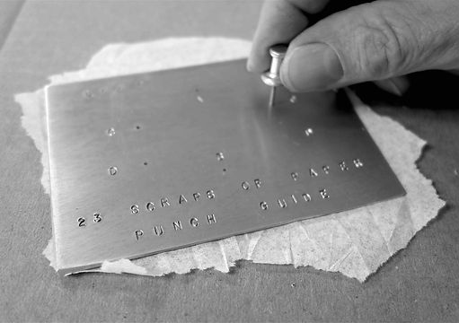 Punching holes in a Scrap of Paper for Machine with 23 Scraps of Paper by Arthur Ganson