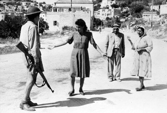 An Israeli soldier stopping Palestinians under curfew, Nazareth, 1948.