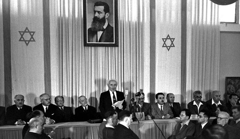 David Ben Gurion, center, a Polish Jew, reads out what Israel called a declaration of independence on May 14, 1948. A photo of Herzl hangs in the backdrop.