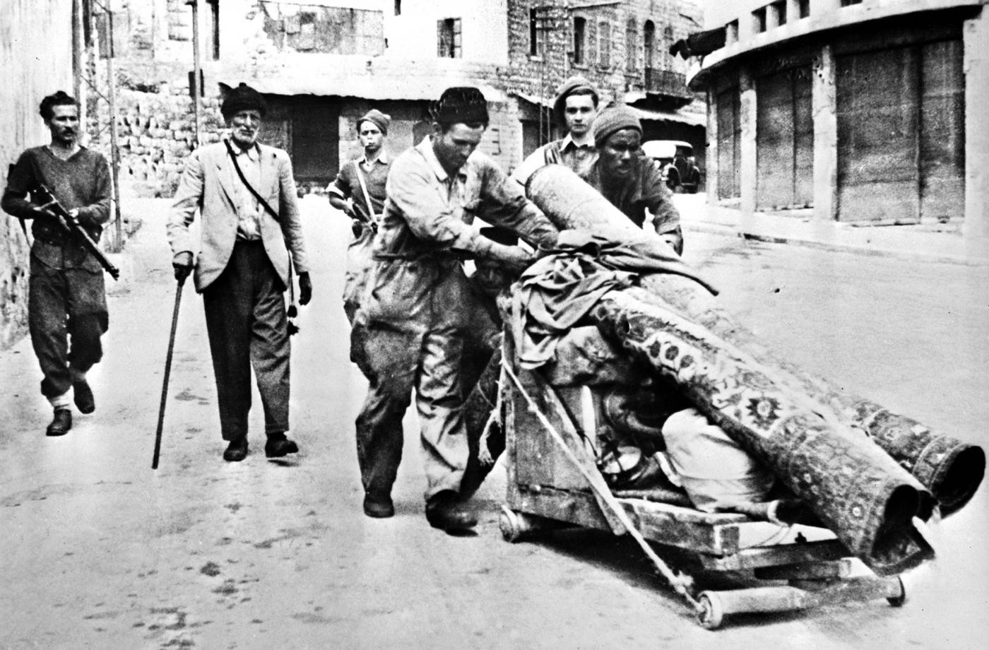 Members of the Haganah paramilitary group escort Palestinians expelled from Haifa after Jewish forces took control in April 1948 (AFP)