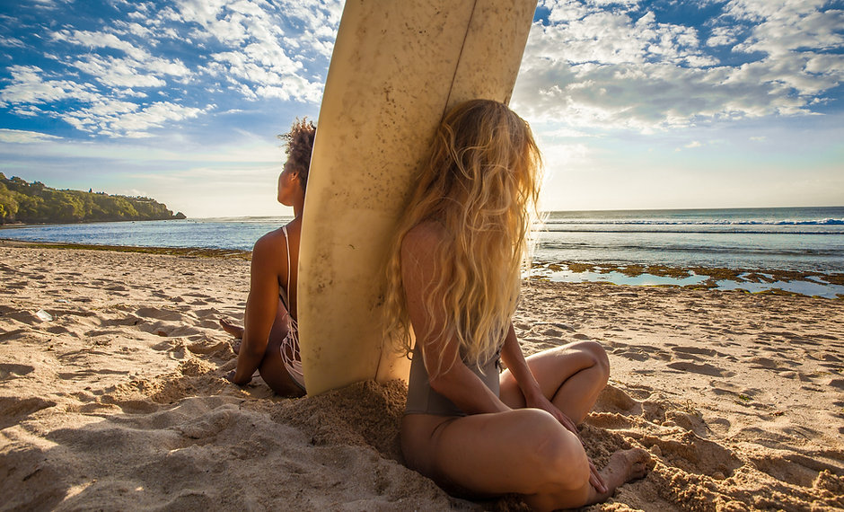 Surfer girls sitting back to back with s