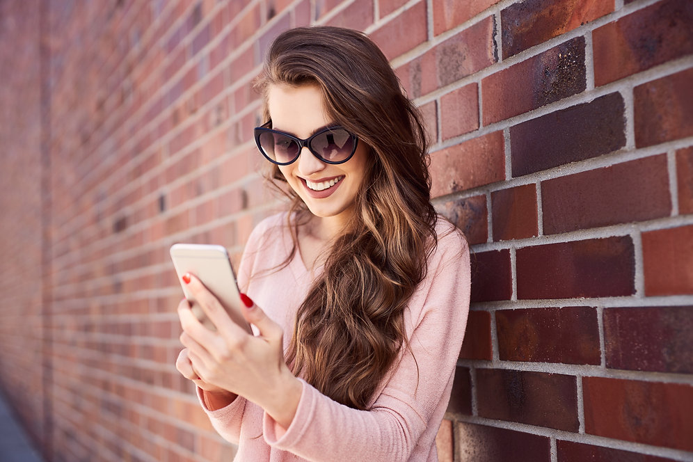 Happy woman using smart phone standing a