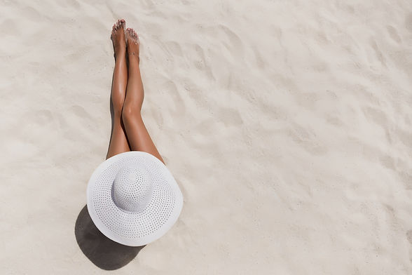 Summer holiday fashion concept - tanning woman wearing sun hat at the beach on a white san