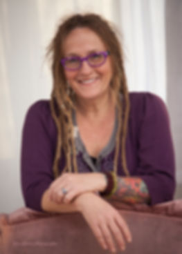 a photo of Jo Hilton looking at camera. Jo is wearing purple sweater and has dreadlocks