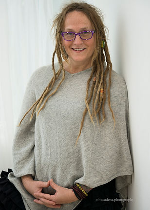a photo of Jo Hilton, a woman wearing a sweater poncho. She has dreadlocks and purple glasses and is smiling at the camera.