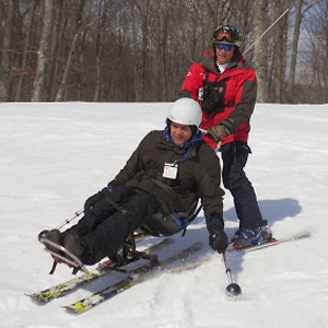 Snow-sitskiier-and-instructor-pushing-to