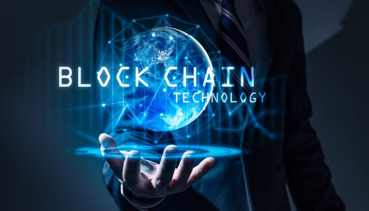 A man is standing with his hand held forward and a holographic globe is projected on top of his hands. The text is at the center of the image and it reads 'Blockchain Technology.''