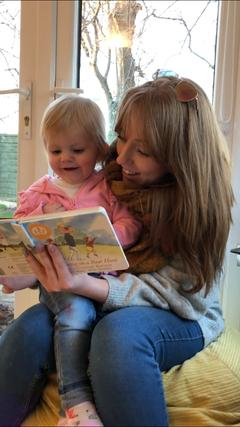 Little bookworm enjoying 'we're going on a bear hunt'
