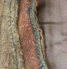 Detail of kirtle neckline, including braid, couching and embroidery