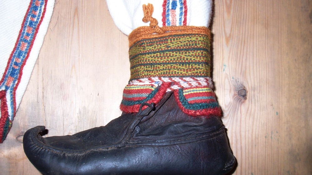 Reproduction of shoes with tablet woven leg bands, braided laces and braids on edges of cuffs