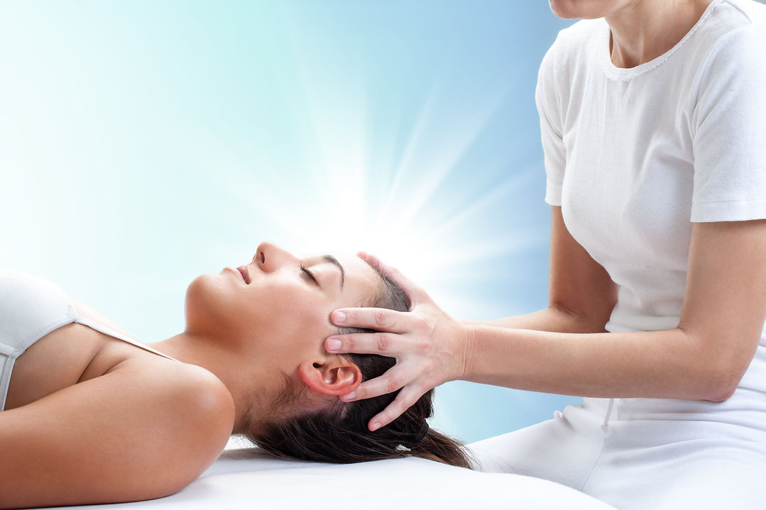 Woman giving another woman Reiki healing