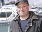 John Galvin stops at the harbor for a photo as he makes his way back from his boat the Rita B. He has contributed to Aleutia for many years.