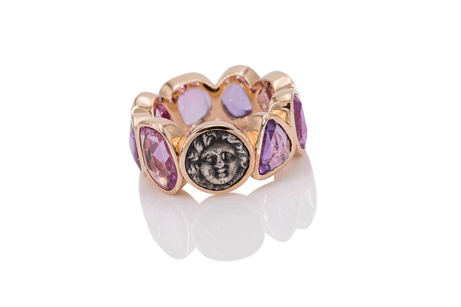 18k GOLD ETERNITY RING | GORGON | SAPPHIRES 8 sapphires 9,97 ct purple-pink ancient greek coin 350-300 b.c.  In Greek mythology, a Gorgon is a female creature. Because of their legendary and powerful gaze that could turn one to stone, images of the Gorgons were put upon objects and buildings for protection.