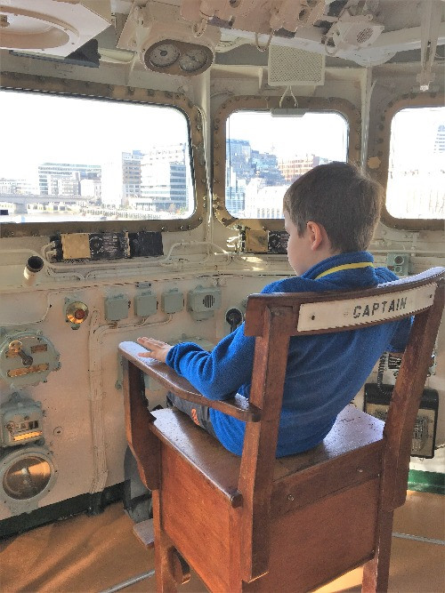 A boy sittig in the Captains chair on the HMS Belfast