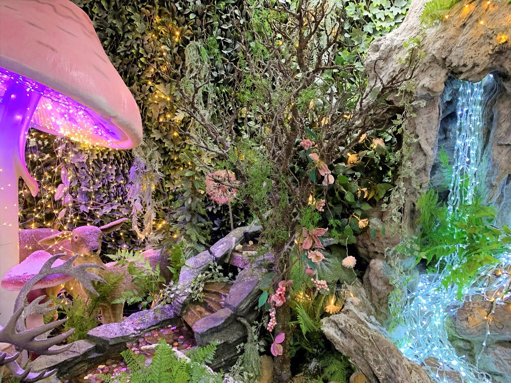 A display with a giant mushroom, waterfall of fairy lights and plants.