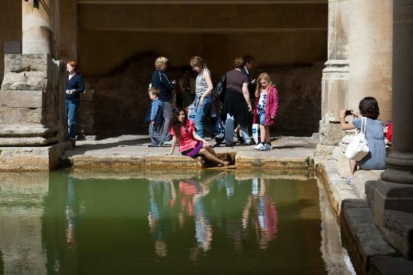 Tourists posing on the edge of the main bath.