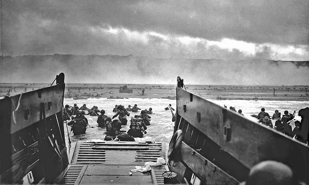 A black and white photo of troops arriving at a beach.