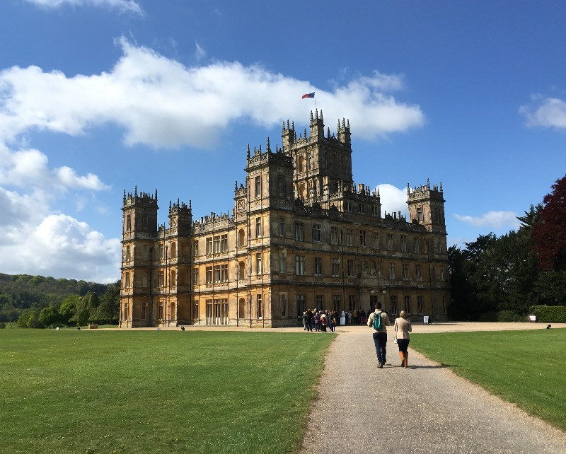 Two people walking up the path to Highclere Castle.